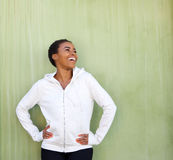 Beautiful young black woman laughing against green wall Royalty Free Stock Photos