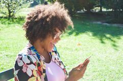 Beautiful young black woman laughing and looking at the smartphone at the park royalty free stock images