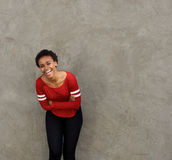 Beautiful young black woman leaning against wall and laughing royalty free stock photos