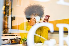 Beautiful young black woman looking at the smartphone drinking coffee at the coffee house stock photos