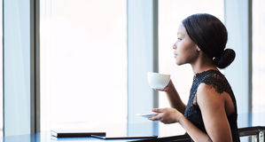 Beautiful young black woman looking thoughtfully out a large window. Highly successful young African American woman looking out the window while drinking her Royalty Free Stock Photo