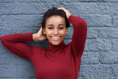 Beautiful young black woman smiling against gray wall with hands in hair Stock Photos