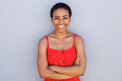 Beautiful young black woman smiling against gray wall. Portrait of beautiful young black woman smiling against gray wall stock photo