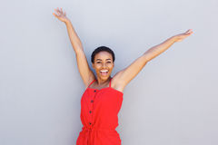 Beautiful young black woman smiling with arms raised Stock Photo