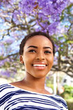 Beautiful young black woman smiling with flower tree in background Stock Photos