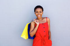 Beautiful young black woman smiling with shopping bags Stock Photo