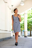 Beautiful young black woman walking outside in striped dress Royalty Free Stock Photography