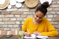 Beautiful young black woman writing notes at cafe. Portrait of beautiful young black woman sitting at cafe and writing notes royalty free stock photo