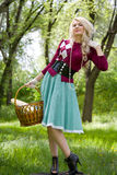Beautiful young blond with basket in summer park royalty free stock photo