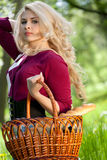 Beautiful young blond with basket in summer park Stock Images