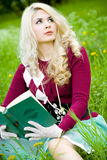 Beautiful young blond with book in summer park Stock Image