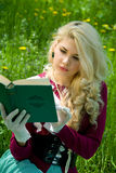 Beautiful young blond with book in summer park royalty free stock photo