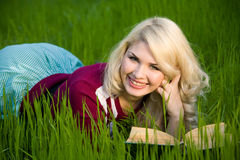 Beautiful young blond with book in summer park Royalty Free Stock Images
