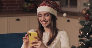 Beautiful Young Blond Caucasian Girl Wearing Santas Hat Sitting near Christmas Tree Using her Smartphone and Smiling stock video
