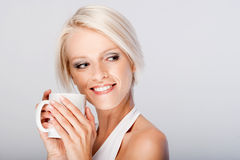 Beautiful young blond enjoying coffee. Beautiful young blond woman cradling a mug in her hands enjoying a drink of freshly brewed coffee,  on white Stock Photos