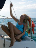 Beautiful young blond female model sunbathing on a yacht in the sea Stock Photo