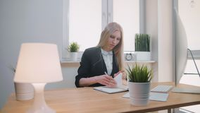 Beautiful young blond female suit sitting at desk writing with pen in notepad, turning page and pulling out sheets of. Paper from her notebook. Woman writing in stock footage