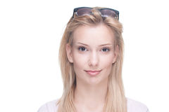 Beautiful young blond girl. Beautiful blond girl with sunglasses on head, white studio background Stock Photography