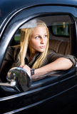 Beautiful young blond girl in a black vintage car. Beautiful young blond girl in a black vintage car, looking away royalty free stock photo