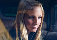 Beautiful young blond girl in a black vintage car. Beautiful young blond girl in a black vintage car, shot through the windscreen royalty free stock photos