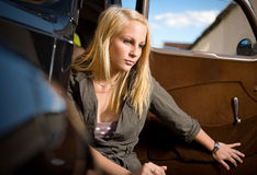 Beautiful young blond girl in a black vintage car. Royalty Free Stock Photography