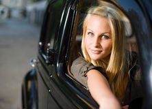 Beautiful young blond girl in a black vintage car. Beautiful young blond girl looking out the window of a black vintage car stock images