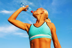 Beautiful young blond girl drinking water Stock Images