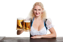 Beautiful young blond girl drinks out of oktoberfest beer stein. Isolated on white background. sits by the table Royalty Free Stock Photos