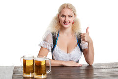 Beautiful young blond girl drinks out of oktoberfest beer stein. Isolated on white background. sits by the table Stock Photography
