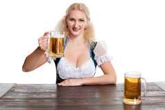 Beautiful young blond girl drinks out of oktoberfest beer stein. Isolated on white background. sits by the table Stock Image