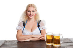 Beautiful young blond girl drinks out of oktoberfest beer stein. Isolated on white background. sits by the table Royalty Free Stock Photo
