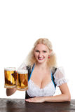 Beautiful young blond girl drinks out of oktoberfest beer stein. Isolated on white background. sits by the table Stock Images