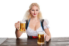 Beautiful young blond girl drinks out of oktoberfest beer stein. Isolated on white background. sits by the table Royalty Free Stock Photography