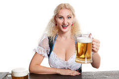 Beautiful young blond girl drinks out of oktoberfest beer stein. Isolated on white background. sits by the table Royalty Free Stock Image