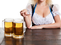 Beautiful young blond girl drinks out of oktoberfest beer stein. Isolated on white background. sits by the table. Close up Royalty Free Stock Image