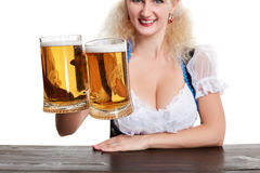 Beautiful young blond girl drinks out of oktoberfest beer stein. Isolated on white background. sits by the table. Close up Royalty Free Stock Images