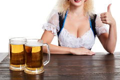 Beautiful young blond girl drinks out of oktoberfest beer stein. Isolated on white background. sits by the table. Close up Royalty Free Stock Photo