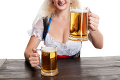Beautiful young blond girl drinks out of oktoberfest beer stein. Isolated on white background. sits by the table. Close up Royalty Free Stock Photography