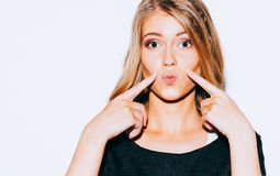 Beautiful young blond girl posing in Sweatshirt and white shorts and red lips kiss does. She points a finger at her lips. Close up Stock Images