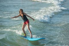 Young girl on a surf board. Beautiful young blond girl riding the waves on a blue surf board Stock Photos