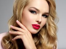 Beautiful young blond girl with sexy red lips. Photo of a beautiful young blond girl with sexy red lips. Closeup attractive sensual face of white woman with Stock Photo