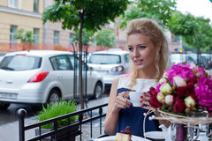 A beautiful young blond girl in summer dress at the table in pav Royalty Free Stock Photography