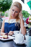 A beautiful young blond girl in summer dress at the table in pav Royalty Free Stock Photo