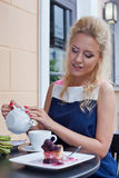 A beautiful young blond girl in summer dress at the table in pav Royalty Free Stock Photos