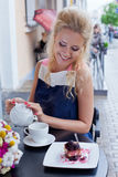 A beautiful young blond girl in summer dress at the table in pav Stock Photography
