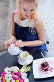 A beautiful young blond girl in summer dress at the table in pav Stock Image
