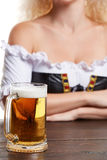 Beautiful young blond girl in traditional costume drinks out of oktoberfest beer stein. Isolated on white background. sits by the table. close-up mug Stock Photo