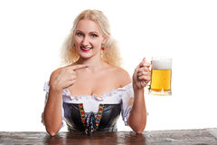 Beautiful young blond girl in traditional costume drinks out of oktoberfest beer stein. Stock Photos