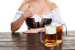 Beautiful young blond girl in traditional costume drinks out of oktoberfest beer stein. Stock Photo