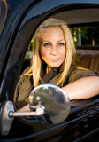 Beautiful young blond girl in a vintage car. Beautiful young blond girl smiling in a black vintage car, looking at the camera stock photos